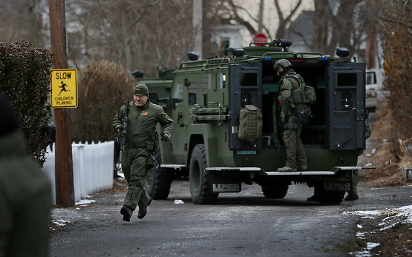 MIKE SPRINGER/Staff photo   <br /> A tactical officer with the Northeastern Massachusetts Law Enforcement Council (NEMLEC) runs from an armored vehicle during a standoff Tuesday afternoon on Munsey Lane, in the Lanesville neighborhood of Gloucester.<br /> 01/15/2018
