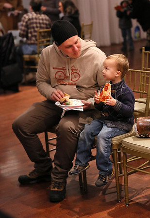 MIKE SPRINGER/Staff photo<br /> Evan Lingenfelter, a seaman based at Coast Guard Station Gloucester, visits with his son Liam, 3, over a slice of pizza Friday at the 10th annual Buoy Auction for Art Haven at Cruiseport Gloucester.<br /> 01/26/2018