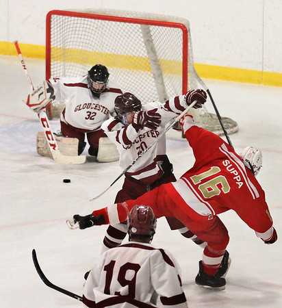 MIKE SPRINGER/Staff photo<br /> Gloucester's Sam Poliskey checks Jason Suppa of Everett as goalie Nathan Noonan handles Suppa's shot -- the first on-goal shot of the game -- during varsity hockey play Wednesday in Gloucester.<br /> 01/03/2018