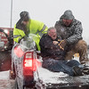 Desi Smith Photo.   Neil Marshall (center) is rescued from four feet of water that trapped him in his apartment on Western Ave, at the height of yesterdays storm. Gloucester Harbor Master, Captain Thomas Ciarametaro, backed his pickup down a driveway in about four feet of icey water to the back door were, Master Deputy Harbormaster Chad Johnson(right) and Detective Jonathan Trefry (left) placed him in back of the truck to transfer him to an awaiting ambulance. January 4,2018