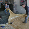 MIKE SPRINGER/Staff photo<br /> From left, Chris Brown, Nick Bonasoro and Steve Brown remove water-logged carpeting from the floor of Shea's Riverside Restaurant & Bar in Essex on Friday morning, a day after Shea's and other downtown businesses were flooded by a historic high tide and storm surge. According to owner Dave Brown, both of the restaurant's dining rooms and the kitchen were flooded by eight to 10 inches of water. Eight refrigerators and the baseboard heating system were destroyed.<br /> 01/05/2018