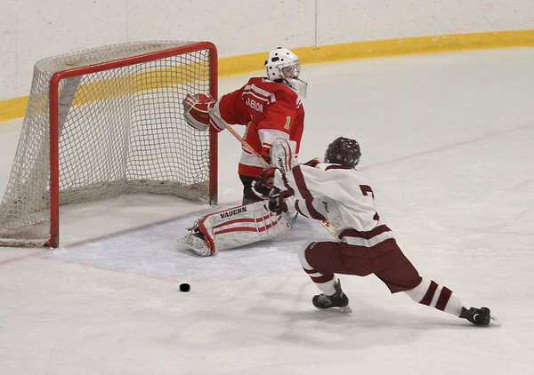 MIKE SPRINGER/Staff photo<br /> A shot by Gloucester's Lucas Cornetta rebounds after being stopped by Everett goalie Brendan Calderone during varsity hockey play Wednesday in Gloucester. Cornetta failed to score on the rebound.<br /> 01/03/2018