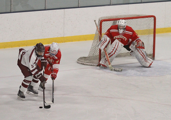MIKE SPRINGER/Staff photo<br /> Gloucester's John John Mondello, left, competes for the puck with Everett's  Brendan Currey under the watchful eye of Everett goalie Brendan Calderone during varsity hockey play Wednesday in Gloucester.<br /> 01/03/2018