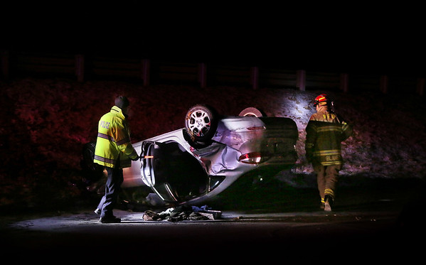 MIKE SPRINGER/Staff photo<br /> A police officer and firefighter investigate the scene of an accident Monday evening in which a car flipped over in one of the southbound lanes of Route 128, just north of Exit 17 at Grapevine Road in Wenham. An ambulance was called to the scene.<br /> 1/15/2018