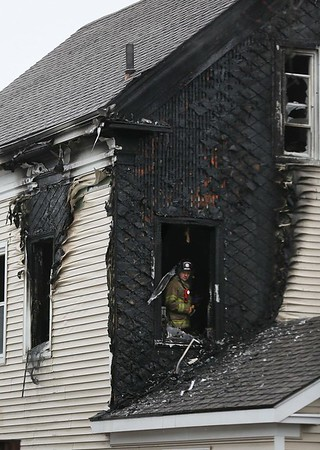 MIKE SPRINGER/Staff photo<br /> A Gloucester firefighter looks out from a second-story window of the house at 33 Grove Street in Gloucester after firefighters put out a fire Tuesday morning.<br /> 01/23/2018 ORG XMIT: 180123_SN_MSP_FIRE [[MER1801231415013507]]
