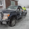 Desi Smith Photo.   Gloucester Firfighter James Hannon in waist deep icey water, directs Gloucester Harbor Master, Captain T.J Ciarametaro, as he backs his pickup down a driveway to a man trapped in his apartment on Western Ave at the height of yesterdays strom. Master Deputy Harbormaster Chad Johnson and Detective Jonathan Trefry are in tha back to pull him in back of the truck and transferd him to an awaiting ambulance.    January 4,2018