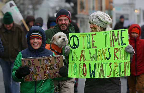 MIKE SPRINGER/Staff photo<br /> From left, 10-year-old Solomon Rich of Rockport, his father Steve (with dog Ozzie) and his mother Amy march together during the Rockport Unitarian Universalist Society's 30th annual march in honor of Rev. Martin Luther King Jr. on Monday in downtown Rockport. In the background at right is Solomon's twin brother, Winston.<br /> 01/15/2018