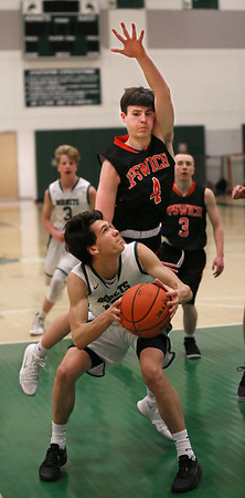 MIKE SPRINGER/Staff photo   <br /> William Janowicz of Manchester Essex prepares to take a shot as Ipswich's Zachary Long towers over him during varsity basketball action Wednesday in Manchester.<br /> 01/10/2018