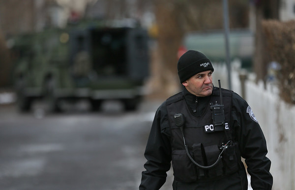 MIKE SPRINGER/Staff photo   <br /> An officer with a Northeastern Massachusetts Law Enforcement Council (NEMLEC) incident management team stands watch Tuesday afternoon at the entrance to Munsey Lane at Washington Street during a standoff Tuesday in Lanesville.<br /> 01/16/2018