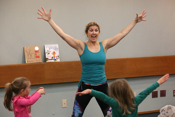 MIKE SPRINGER/Staff photo<br /> Erin McKay of Treetop Yoga in Gloucester leads a group of children in a special yoga for toddlers event Wednesday at the Sawyer Free Library. In the foreground are four-year-olds Audreyana Beloff, left, and Elodie Galbraith.<br /> 01/25/2018
