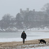 MIKE SPRINGER/Staff photo<br /> Patty Halleran of Hamilton walks with her chocolate labrodor, Bella Brown Bear, on Singing Beach in Manchester during Wednesday's snowfall.<br /> 01/17/2018