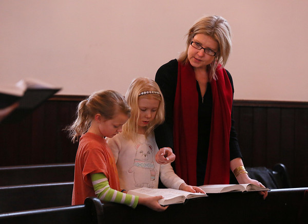 MIKE SPRINGER/Staff photo<br /> Kezia Evans helps her 8-year-old daughter Scarlett Berge, center, and Scarlett's friend Opal Wilkinson, 10, follow along in the hymn book during a service Mondayt honoring the Rev. Martin Luther King Jr. at the Unitarian Universalist church in Rockport.<br /> 01/15/2018