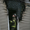 MIKE SPRINGER/Staff photo<br /> Firefighter Ryan Goodwin examines the damage around a second-floor window of the house at 33 Grove Street in Gloucester after firefighters put out a fire Tuesday morning.<br /> 01/23/2018