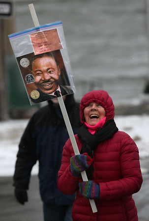 MIKE SPRINGER/Staff photo<br /> Nancy Rote of Rockport carries a picture of Martin Luther King, Jr. during the Rockport Unitarian Universalist Society's 30th annual march in King's honor Monday in downtown Rockport.<br /> 01/15/2018