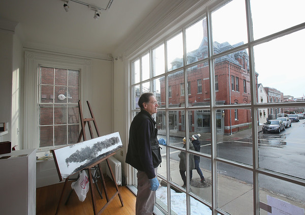 """MIKE SPRINGER/Staff photo<br /> Artist George Wingate of Wenham looks out Thursday onto the corner of Pleasant and Middle streets from the front window of his temporary space at the Jane Deering Gallery in Gloucester. Wingate, whose work has been featured in solo exhibits in New York, San Francisco, Italy and elsewhere, says he's viewing his month at the Deering gallery as a kind of fellowship. """"I want to be receptive,"""" he said, """"and let what happens happen.""""<br /> 01/11/2018"""