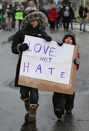 "MIKE SPRINGER/Staff photo<br /> Shoshy Collins and her son Isaac, 6, carry a sign saying ""Love Not Hate"" during the Rockport Unitarian Universalist Society's 30th annual march in honor of Rev. Martin Luther King Jr. on Monday in downtown Rockport.<br /> 01/15/2018"