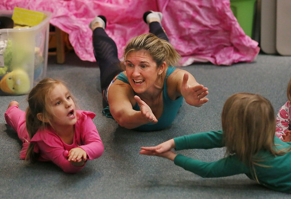 MIKE SPRINGER/Staff photo<br /> Erin McKay of Treetop Yoga leads four-year-old Audreyana Beloff, left, and Elodie Galbraith, both 4, in a yoga for toddlers class Wednesday at the Sawyer Free Library in Gloucester.<br /> 01/25/2018