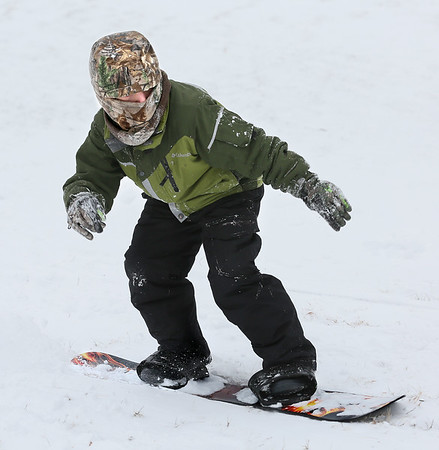 MIKE SPRINGER/Staff photo<br /> Bundled up for the cold, 9-year-old Gryphon Orfanos rides his snowboard down the hill at Stage Fort Park in Gloucester following Tuesday's snowfall.<br /> 01/30/2018