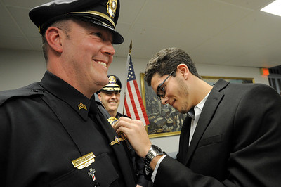 Jason Mahoney pins his father's, Dan Mahoney, new badge on during a selectman meeting where Officer Dan Mahoney was promoted to Sargent at Rockport Town Hall on Tuesday January 8, 2019.  Photo by Joseph PREZIOSO
