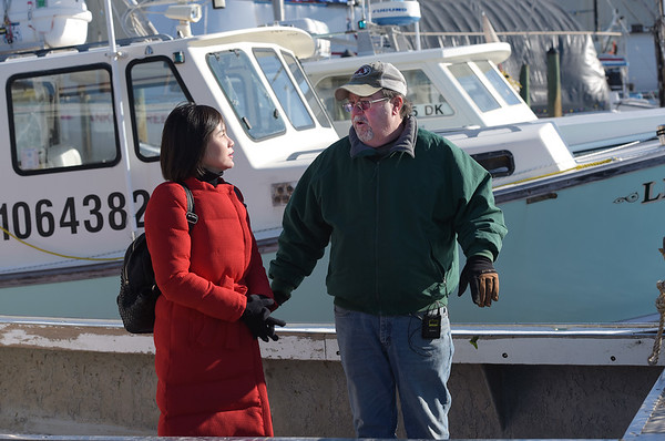 TIM JEAN/Staff photo<br /> <br /> China Central Televison correspondent Zhu Xili, left, talks with with Lobster Boat Captain Mark Ring, of Gloucester, while camera operator Mu Lyu, films them for an upcoming a TV show on lobsters.     1/31/19