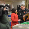 TIM JEAN/Staff photo<br /> <br /> China Central Televison correspondent Zhu Xili, center, and camera operator Mu Lyu, left, film Vince Mortillaro, owner of Mortillaro Lobster Company in Gloucester. Mortillaro demonstrated the process of how they ship live lobsters to China.    1/31/19