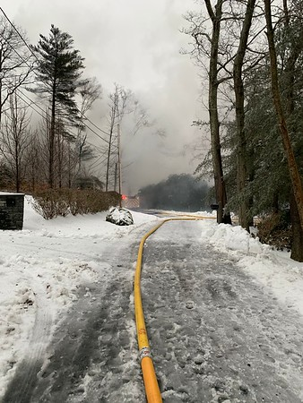 MICHAEL CRONIN/Staff photo/Smoke rise from a hoom destroyed by fire on University Lane in Manchester. Firefighters ran lines down the street to get water to the scene.