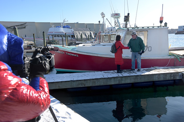 TIM JEAN/Staff photo<br /> <br /> China Central Televison correspondent Zhu Xili, center, shakes hands with Lobster Boat Captain Mark Ring, of Gloucester, as camera operator Mu Lyu, films them for an upcoming a TV show on lobsters.     1/31/19