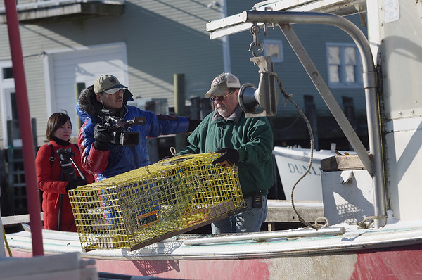 TIM JEAN/Staff photo<br /> <br /> China Central Televison correspondent Zhu Xili, left, and camera operator Mu Lyu, film Lobster Boat Captain Mark Ring, of Gloucester, for an upcoming a TV show on lobsters.     1/31/19
