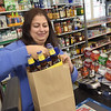 TIM JEAN/Staff photo<br /> <br /> Dina Hanna, owner of Good Harbor Liquors in Gloucester, bags items for a customer in a brown paper bag. Some stores are having issues with the new plastic bag ban. 1/29/19