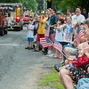 DESI SMITH/Staff photo.  Edith Fouser (right) of Essex, covers her 18 month old son Keppler's ears, as fire trucks from different towns honk their horns and sirens in the 4th of July Parade, as they pass the crowd of spectators on School Street in Manchester Friday morning . <br />   July 4,2014
