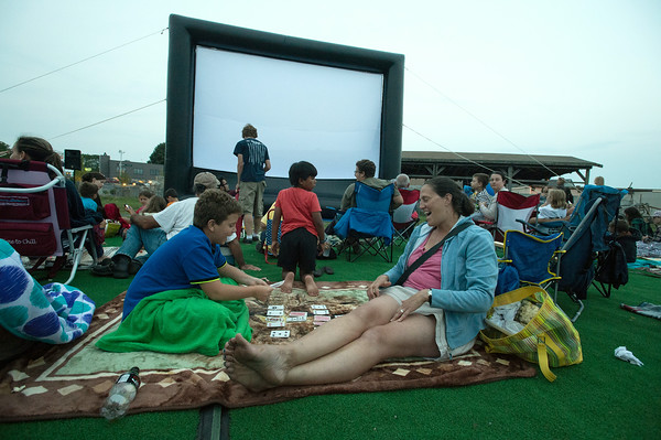 "DESI SMITH/Staff photo.   Nora Priest and her son Josh 9, of Gloucester, play a game of garbage, while waiting for the start of ""Back to the Future"" at the outdoor movie showing on I-4 C-2 property Wednesday night, as part of city-sponsored Summer Cinema Series.  July 19,2014"