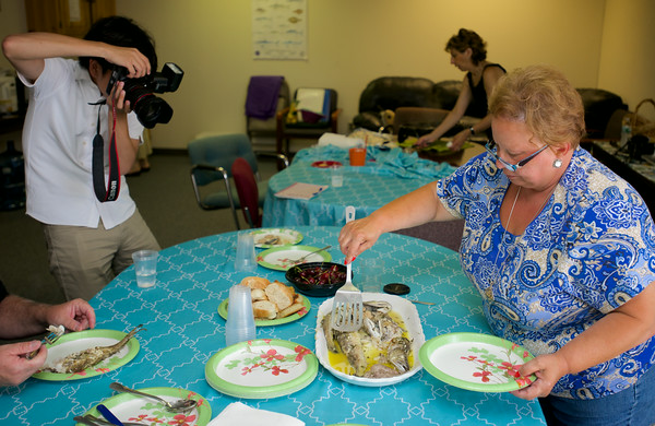 RYAN HUTTON/ Staff photo.<br /> Japanese journalist Akifumi Hoshina takes photographs of Angela Sanfilippo serving up  hake fish in the kitchen of the Gloucester Fishermen's Wives Association' offices.