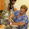 RYAN HUTTON/ Staff photo.<br /> Japanese journalist Akifumi Hoshina records video of Angela Sanfilippo cleaning hake fish before cooking them in the kitchen of the Gloucester Fishermen's Wives Association' offices.