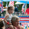 DESI SMITH/Staff photo. Catherine Dalaney 2, of Manchester, waves her flag, as she watchers the 4th of July Parade on her grandfather Barett Petty shoulders on School Street in Manchester Friday morning. <br />   July 4,2014
