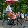 DESI SMITH/Staff photo.  Eliza Troctor of Manchester, rides one of Bill Burrow's vintage bikes, looking a little like Mary Poppin's, in the Manchester's 4th of July Parade on School Street Friday morning. <br />   July 4,2014