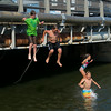 RYAN HUTTON/ Staff photo.<br /> From left, Issac Notte, 12, Andrew Amigo, 10, Abbey Amigo, 7, and Issac Amigo, 9, of Essex, jump from the Main Street bridge into the causeway to stay cool in Essex on Wednesday.