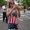 DESI SMITH/Staff photo. Trish Gately wears her stars and strips as she leads the Tony Barrie Band of Saugas, while playing the trumpet in the 4th of July Parade Friday morning in Manchester. <br />   July 4,2014