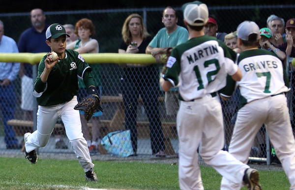 DAVID LE/Staff photo. Manchester-Essex first baseman Thomas Steriti flips the ball towards second baseman Trip Graves as he covers first against Beverly in the District 15 Final on Thursday evening. 7/14/16.