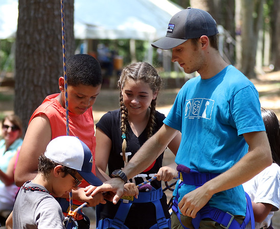 DAVID LE/Staff photo. O'Maley middle school rising 6th graders Elijah Hughes, second from left, and Ella Grossi, second from right, help Dillon Engelmann, Youth and College Program coordinator for Project Adventure, strap in classmate Michael Francis as he prepares to make a climb on Friday afternoon. 7/22/16.