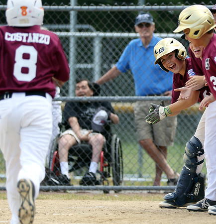 DAVID LE/Staff photo. Gloucester players excitedly wait at home plate for Jack Costanzo after he launched a homer in the top of the 7th inning to give Gloucester a 1-run lead in extra frames. 7/2/16.