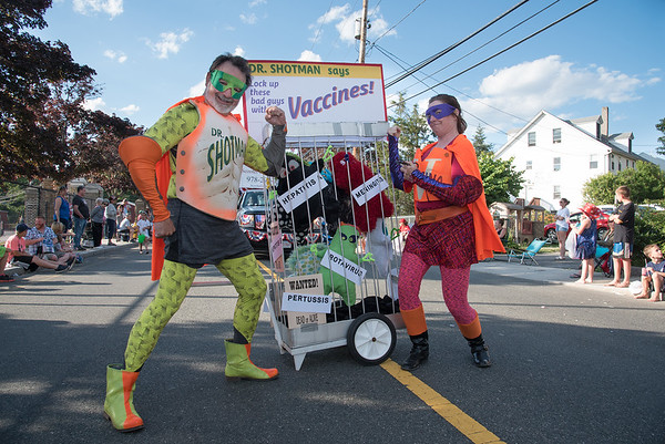 Desi Smith Photo.    Dr. Jeffrey Stockman a Gloucester pediatrician, along with his wife Linda, show off their super powers as they promote getting a vaccine shot on Centenial Ave in the Fishtown Horribles Parade Sunday afternoon.     July 3,2016