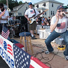 Desi Smith Photo.     Gary Richards plays the harmonica with the band known as Senator Bruce Tarr's Band as they head down Centenial Ave from Gloucester High School in the Fishtown Horribles Parade Sunday afternoon.     July 3,2016