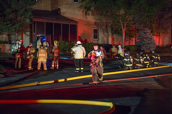 Desi Smith Photo.      Firefighters from Essex,Gloucester,Rockport and Hamilton/Wenham stand by at a business complex located at 239 Western Ave in Essex, as they fight a 2 alarm fire Monday night on the fourth of July.