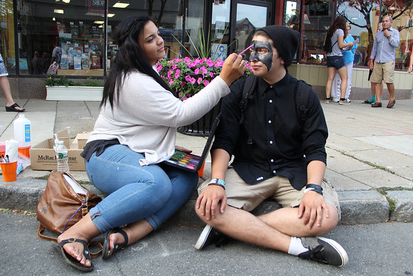 Artist Jasmine White, left, paints Anthony Curcuru's face during the block party. Vincenzo Dimino/Photo