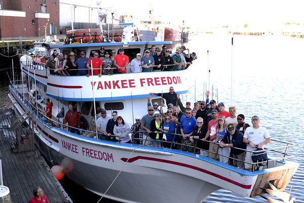 PAUL BILODEAU/Staff photo. A group of veterans and their families head pose for a photo on the Yankee Freedom on the backside of the State Fish Pier before  heading  out fishing for the day. Dave Marciano of Wicked Tuna and Tom Orrell of the Yankee Fleet hosted a fishing trip to benefit the Wounded Warrior Project.