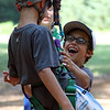 DAVID LE/Staff photo. O'Maley Academy student and rising 6th grader Michael Francis, right, runs to greet classmate Jason Earl, after he made the first climb of the afternoon at Project Adventure in Beverly. 7/22/16.