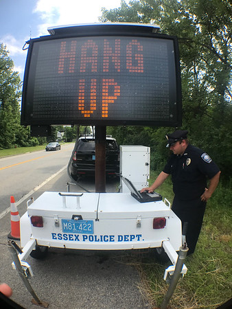MARY MARKOS/Courtesy photo<br /> Essex police Officer James Romeos programs the department's electronic sign board on John Wise Avenue, Route 133, to deliver a message from to residents, and visitors, entering town: Hang Up On Fraud. Police Chief Peter G. Silva says phone scams are big source of fraud.