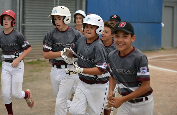 RYAN HUTTON/ Staff photo<br /> Gloucester's Zach Morris, center, trots with his teammates back to the bench after he hit a three-run homer during the top of the first inning of Saturday night's Section 4 Little League championship against Peabody at Wyoma Field.