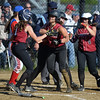 RYAN HUTTON/ Staff photo<br /> Gloucester's Samantha Cominelli is swarmed by teammates at home after hitting a three-run homer in the bottom of the third inning of Wednesday's home tournament game against Burlington.