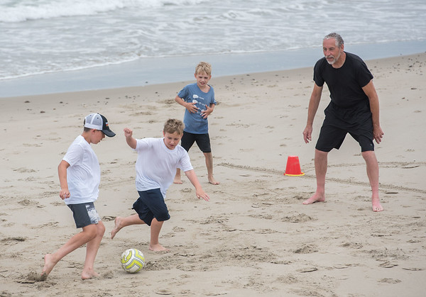 AMANDA SABGA/Staff photo<br /> <br /> John Terry, of Belmont, plays a game of soccer on Long Beach in Rockport with his grandsons, from left, Ben, 10, Ryan, 9, and Colin, 7. <br /> <br /> 7/18/19